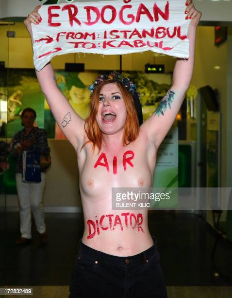 A feminist activist from the radical protest group Femen holding a placard reading 'Erdogan from Istanbul to Kabul' and with the words 'Air Dictator'...