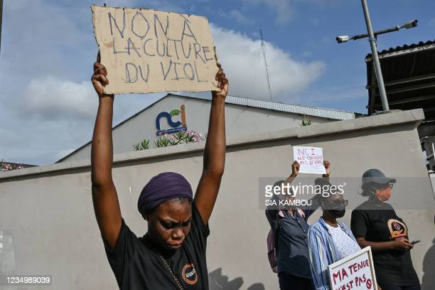 """Feminist activist holds a placard reading """"No to rape culture"""" during a demonstration against the television channel Nouvelle Chaine Ivorienne..."""