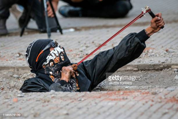 TOPSHOT A feminist activist uses a slingshot during a protest against gender violence and patriarchy in Santiago on November 29 2019 Furious Chileans...
