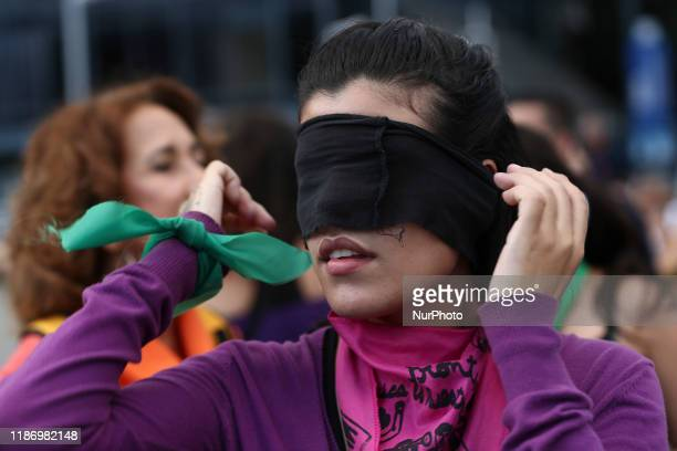 Feminist activist with her eyes covered, takes part in a choreographed performance at the Venezuela square against gender violence and patriarchy in...