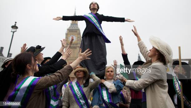 Feminist activists dressed as The Suffragettes women who historically demanded the right to vote protest at Parliament Square for women's rights and...