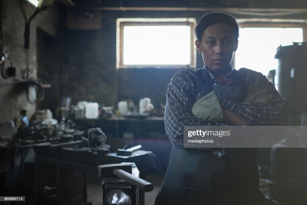 Feminist working in smithy : Stock Photo