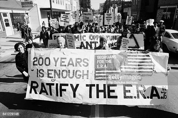 Feminists carry a banner for the Equal Rights Amendment during a civil rights march commemorating the birthday of Martin Luther King Jr in an Atlanta...