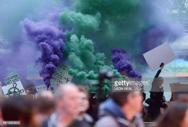Feminists light smoke flares and protest on the sidelines of the premiere of 'Suffragette' at the London Film Festival in central London on October 7...