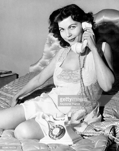 Femme assise sur son lit et téléphonant