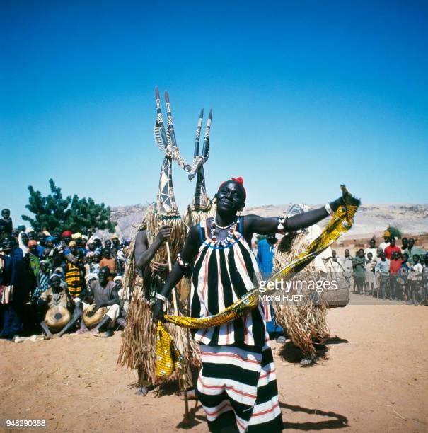 Femme dansant devant deux danseurs traditionnels Kurumba portant des cimiers d'antilope Adone circa 1950 à Arbinda Burkina Faso