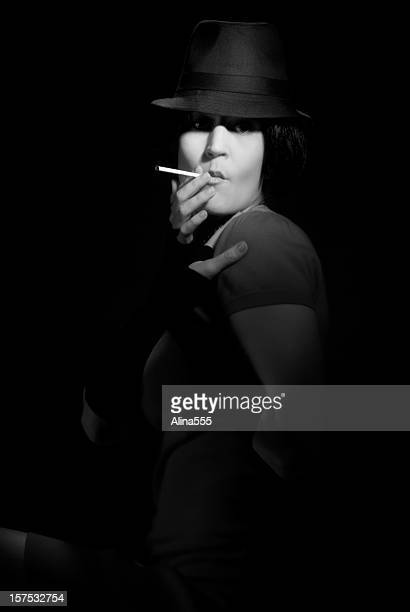 femme fatal: beautiful woman wearing fedora on black background - 1940s erotica stock photos and pictures