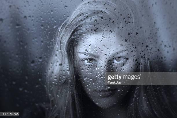 Femme Fatale behind Wet Glass