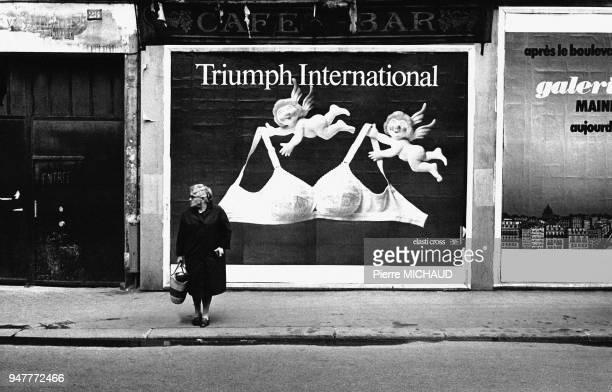 Femme âgée devant une affiche publicitaire de lingerie dans la rue en France