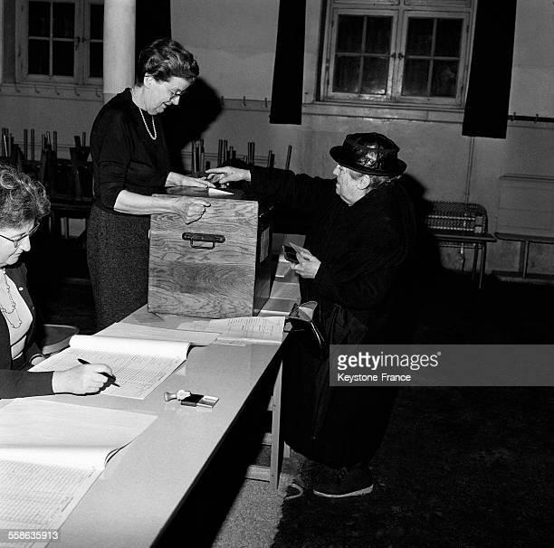 Femme âgée mettant un bulletin de vote dans une urne à l'occasion de l'élection présidentielle en France le 5 decembre 1965