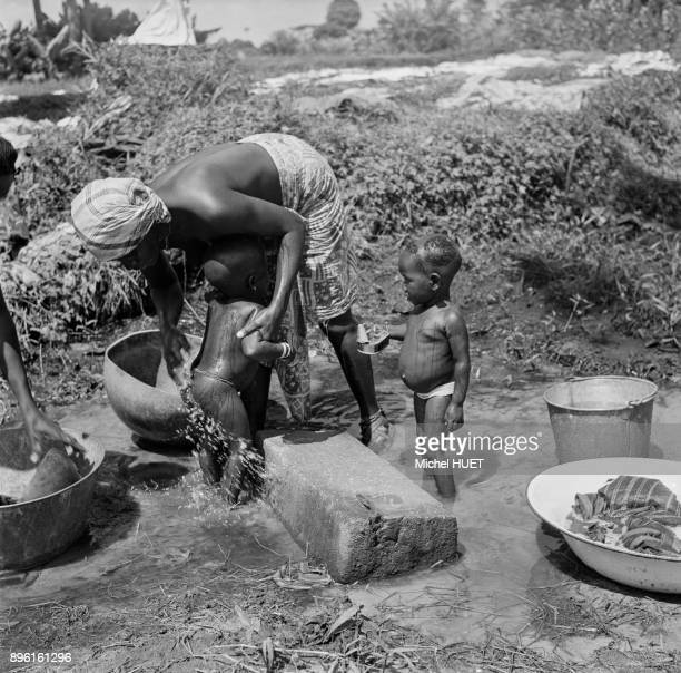 Femme lavant ses enfants dans une riviere en Cote d'Ivoire circa 1950