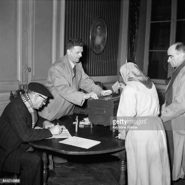 Femme mettant son bulletin dans l'isoloir ans un bureau de vote à Paris France le 2 janvier 1956