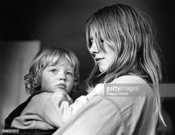 Femme portant sa fille dans les bras en 1985