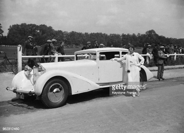 Femme posant devant une belle voiture au Bois de Boulogne à Paris France le 10 juin 1936