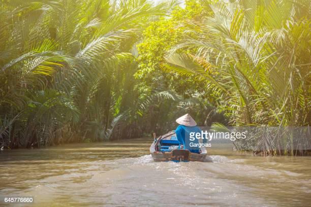 Femme qui conduit un bateau dans le delta du Mékong