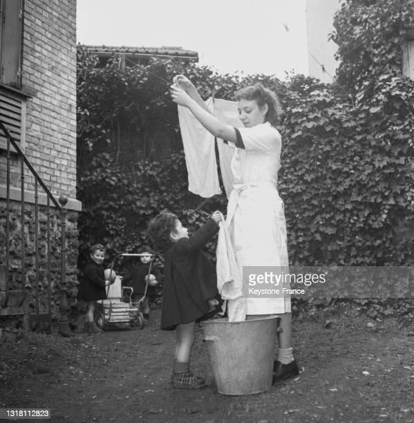 Femme étandant le linge dans son jardin, en février 1949.