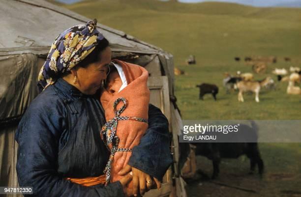 Femme tenant son bébé dans les bras devant sa yourte en Mongolie