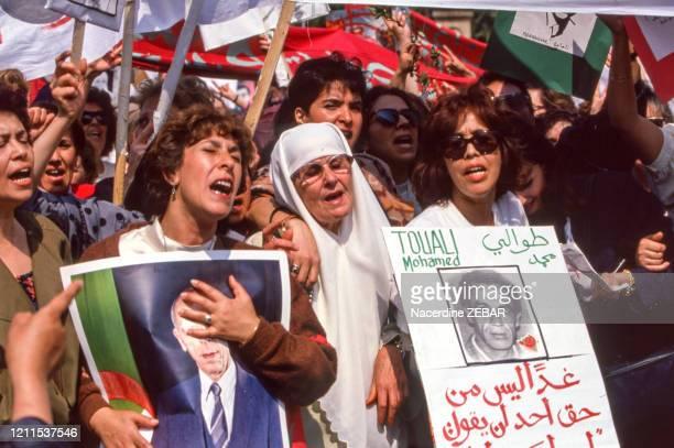 Femme tenant un portrait du président algérien Mohamed Boudiaf assassiné par un islamiste durant une manifestation contre le terrorisme et...
