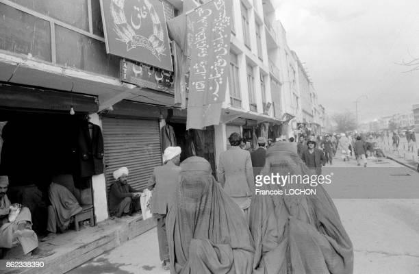 Femmes en burqa devant une banderole de propagande sur la façade du siège du Parti communiste afghan le 3 avril 1979 à Kaboul Afghanistan
