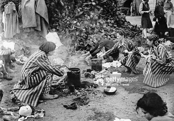 Femmes juives préparant leur repas derrière une pile de chaussures ayant appartenu à des internés morts dans le camp de BergenBelsen circa 1940...
