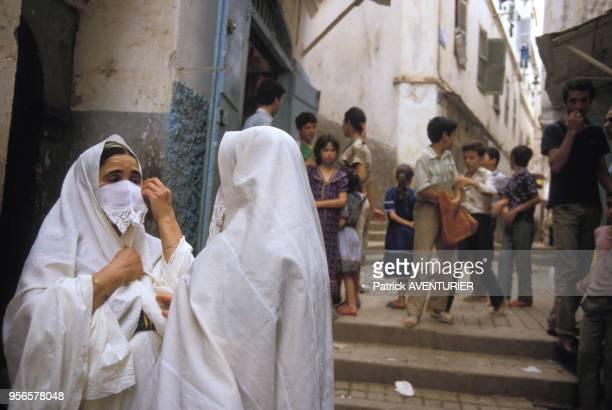 Femmes portant le haïk voile traditionnel blanc dans une rue d'Alger en juillet 1985 en Algérie