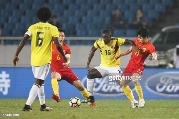 Fen Xiaoting of China National Team and Duvan Zapata of Columbia National Team compete for the ball during the international friendly match between...