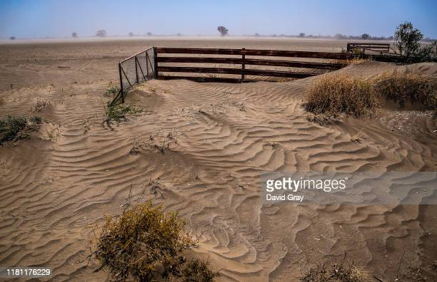 Fence and gate are covered in wind-blown soil as a dust storm blows though a drought-affected property located on the Moree Plains and on the...