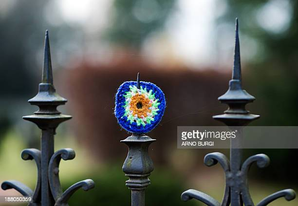 Afence at the Soviet garrison cemetary is decorated with a yarn bombing or knitted graffiti in Dresden Germany on November 14 2013 Guerilla Knitting...