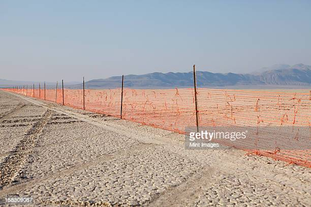 Fence barricade extending across the flat landscape, Black Rock Desert, Nevada.