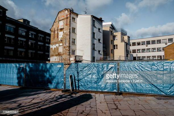 fence by incomplete buildings at construction site in city - albrecht schlotter stock photos and pictures