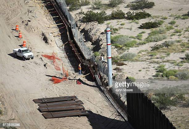 A fence construction worker on the American side speaks to an unidentified person on the Mexican side at the USMexico border fence on October 4 2016...