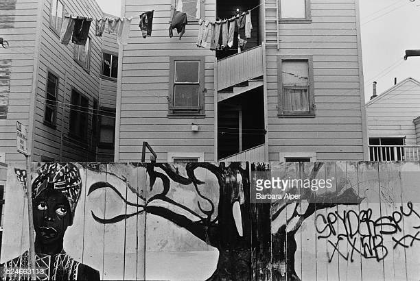 A fence decorated with a mural in the Mission District San Francisco California USA 13th October 1991