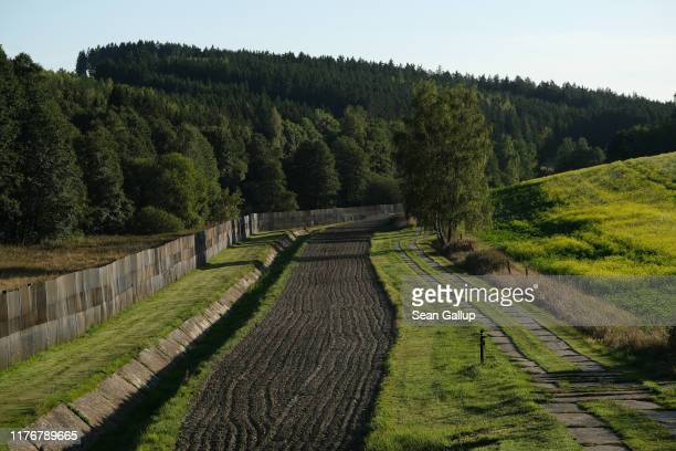 A fence ditch smoothened earthen track and patrol road stand as a memorial along the former fortified border between East Germany and West Germany on...