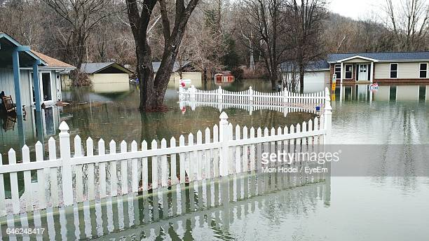 fence in water amidst houses during flood - extreme weather stock photos and pictures