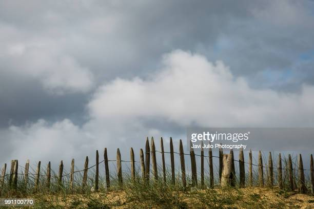 a fence next to a dune of the beach of capbreton, in france - 待避所標識 ストックフォトと画像
