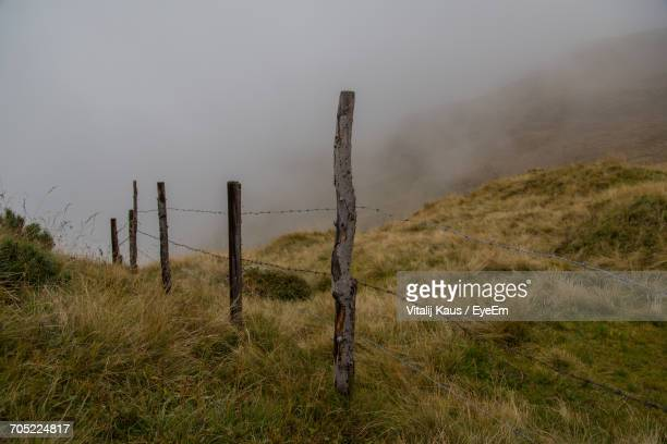 Fence On Field Against Cloudy Sky