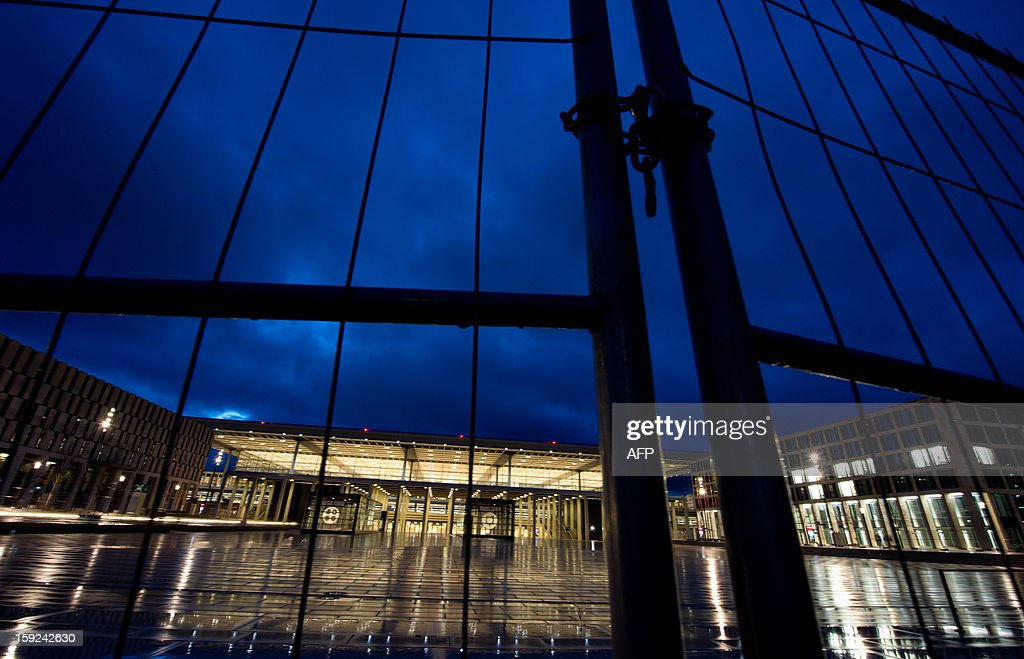 A fence protects the construction site of the terminal building of the new 'Willy Brandt' Berlin Brandenburg International (BER) airport on January 10, 2013 at dawn. The opening of the Berlin Brandenburg Willy Brandt (BER) airport has been postponed indefinitely after several previous delays, the city's mayor said early January 2013, in a fresh blow for the German capital and its top official.