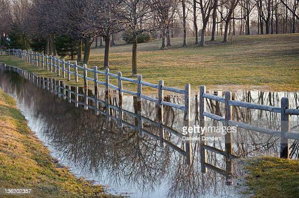 Fence reflected in puddle