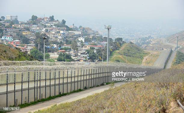 A fence runs along the USMexico border between the Otay Mesa and San Ysidro ports of entry in and near San Diego California across from Tijuana...