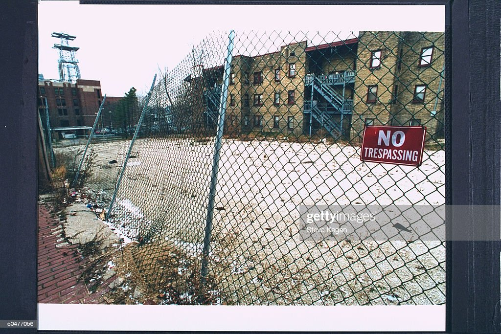 Fence-bordered vacant lot sporting a NO TRESSPASSING sign, formerly the site of the apartment bldg. where serial killer & cannibal Jeffrey Dahmer resided & mutilated his victims.