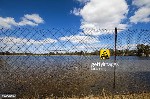 a fenced off area and poison warning sign at the robinson dam in randfontein, south africa which is highly toxic due to years of acid mine drainage. - acid warning stock photos and pictures