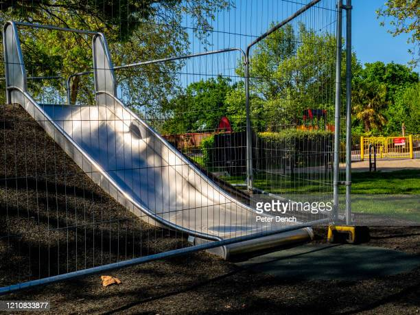 """Fenced-off children's slide in Finsbury Park on April 22, 2020 in London, England. Taped-off benches and other """"social distancing"""" markers have..."""