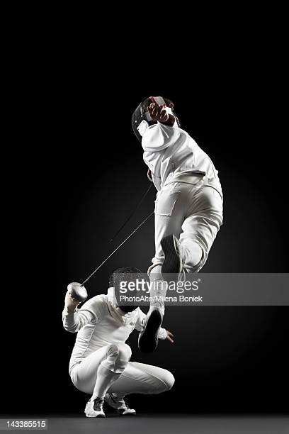 Fencers fencing, one fencer jumping in air