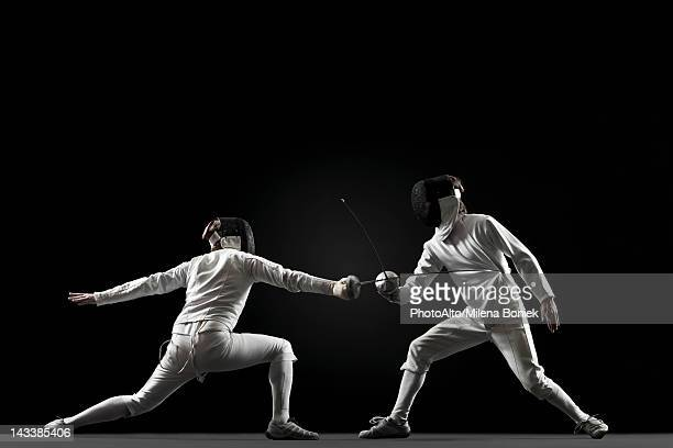 fencers fencing - rivalry stock pictures, royalty-free photos & images