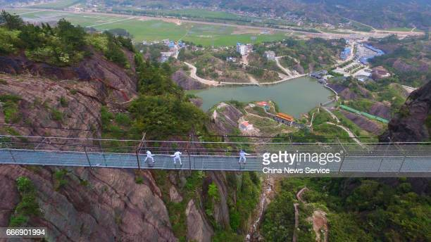 Fencers practice on a glassbottomed skywalk at Shiniuzhai National Geological Park in Pingjiang County on April 7 2017 in Yueyang Hunan Province of...
