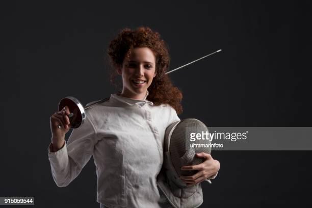 Compétition d'escrime sport. Fond gris foncé. Femmes sportives. Escrimeur de filles portrait rousse bouclés.