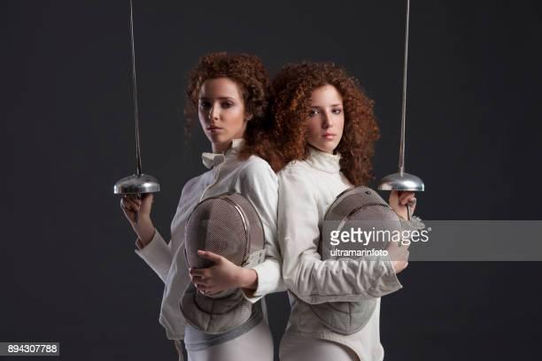 competição de esporte de esgrima. duelo. fundo cinzento escuro. ostentando as mulheres. esgrimista de meninas gêmeas duas ruivas encaracolado. gêmeos. - esgrima esporte de combate - fotografias e filmes do acervo