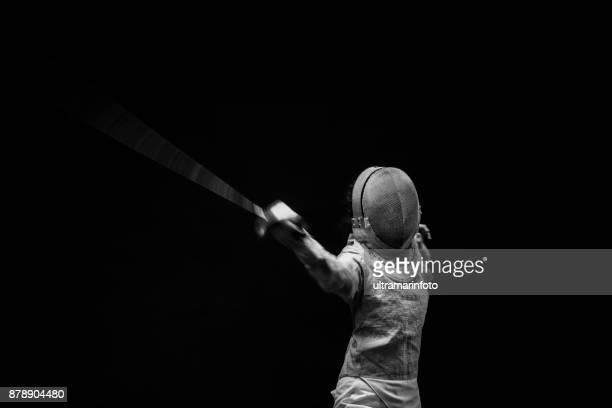 Esgrima deporte joven acción tirador en pose de esgrima.  Fondo negro.