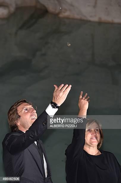 Fendi's Ceo Pietro Beccari and Silvia Venturini Fendi throw coins into the restored Trevi fountain during its inauguration on November 3 2015 in...