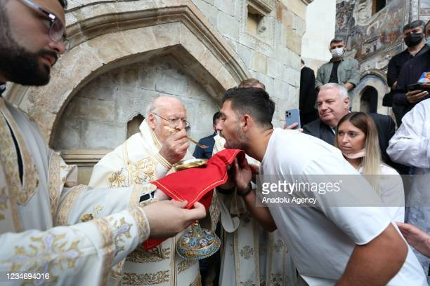 Fener Greek Patriarch Bartholomew and soccer player Anastasios Bakasetas of Trabzonspor are seen during the mass held for the Assumption of Mary for...